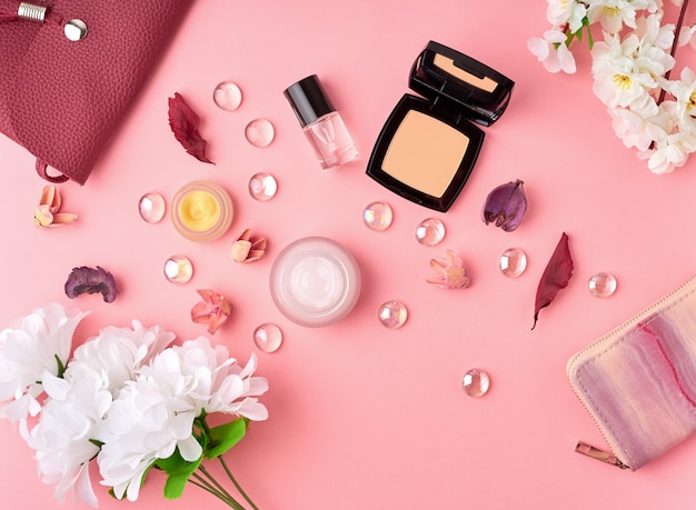 Flat lay woman accessories with cosmetic, facial cream, bag, flowers on bright pink table.