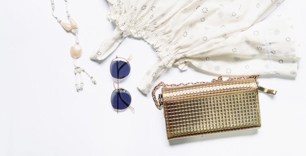 Flat lay of woman clothes and accessories set with glasses, handbag.