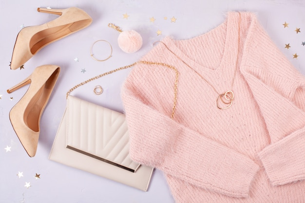 Flat lay of woman clothing and accessories in pastel colors