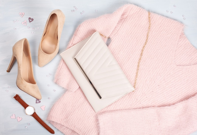 Flat lay of woman clothing, accessories in pastel