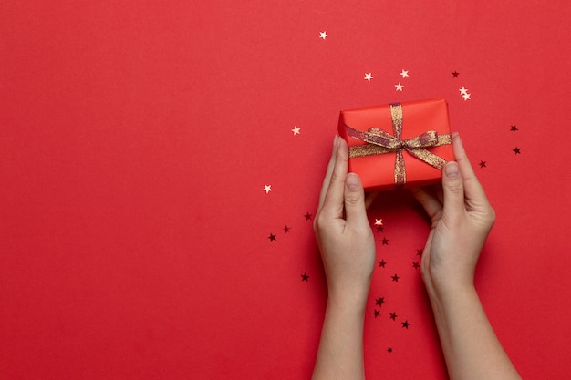 Flat lay of woman hands holding surprise gift box wrapped and decorated with bow with gold stars on red background. birthday, valentines day, christmas, new year. flat lay style