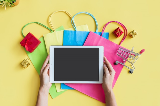 Flat lay of woman hands using tablet with miniature gift boxes. trolley and colorful bags on yellow background. top view and copy space for text. online shopping, new normal, lifestyle concept.