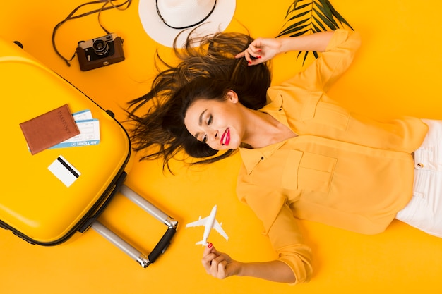 Flat lay of woman posing next to travel essentials