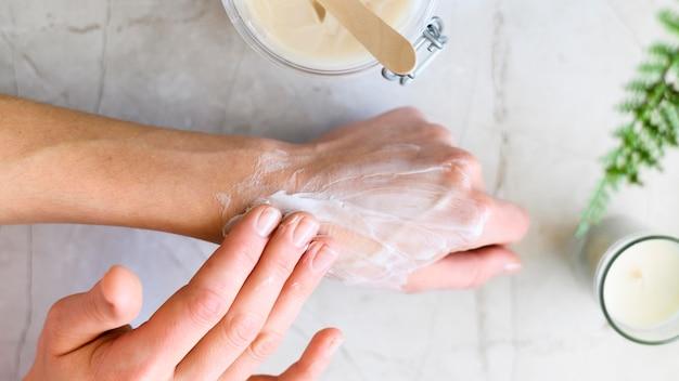 Disposizione piana della donna che mette crema sulle sue mani