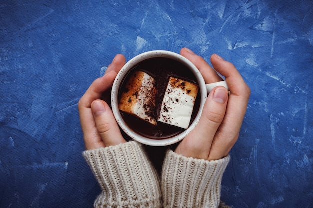 Flat lay of woman's hands in sweater holding cocoa or hot chocolate with homemade vegan marshmallow