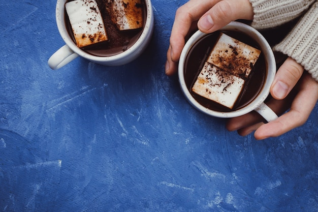 Flat lay of woman's hands in sweater and two cups of cocoa or hot chocolate with homemade vegan marshmallow