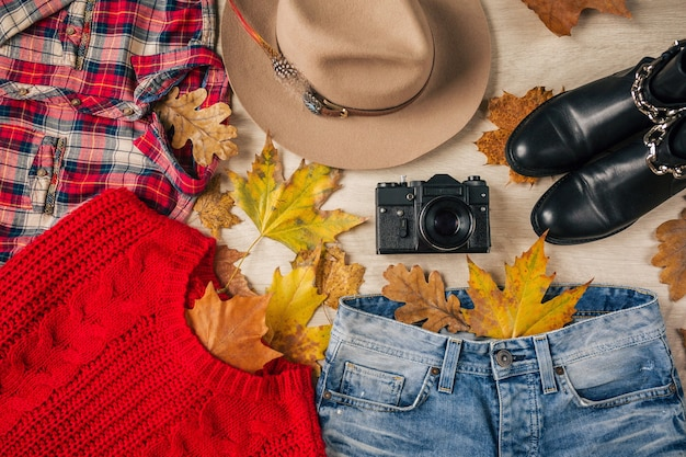 Flat lay of woman style and accessories, red knitted sweater, checkered shirt, denim jeans, black leather boots, hat, autumn fashion trend, view from above, clothes, yellow leaves