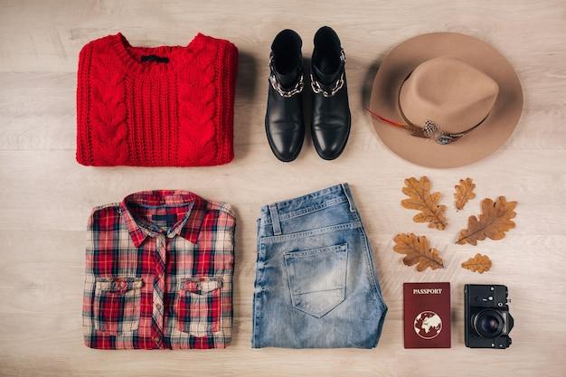 Piatto di stile donna e accessori, maglione rosso lavorato a maglia, camicia a scacchi, jeans in denim, stivali in pelle nera, cappello, tendenza moda autunnale, vista dall'alto, macchina fotografica vintage, passaporto