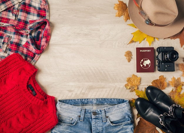 Flat lay of woman style and accessories, red knitted sweater, checkered shirt, denim jeans, black leather boots, hat, autumn fashion trend, view from above, vintage photo camera, passport
