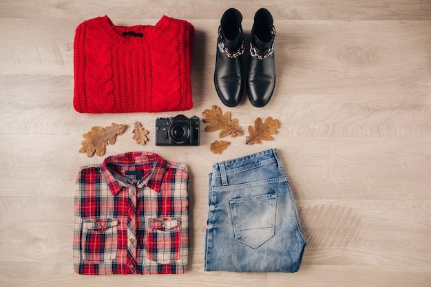Lay piatto di stile donna e accessori, maglione rosso lavorato a maglia, camicia a scacchi, jeans in denim, stivali in pelle nera, cappello, tendenza moda autunnale, vista dall'alto, macchina fotografica vintage, vestito da viaggiatore