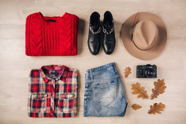 Flat lay of woman style and accessories, red knitted sweater, checkered shirt, denim jeans, black leather boots, hat, autumn fashion trend, view from above, vintage photo camera, traveler outfit