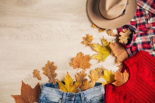 Lay piatto di stile donna e accessori, maglione rosso lavorato a maglia, camicia a scacchi, jeans denim, cappello, tendenza moda autunno, vista dall'alto, vestiti, foglie gialle