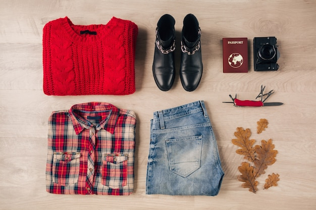 Flat lay of woman style and accessories, red knitted sweater, checkered shirt, jeans, black leather boots, autumn fashion trend, vintage photo camera, swiss knife, passport, traveler outfit
