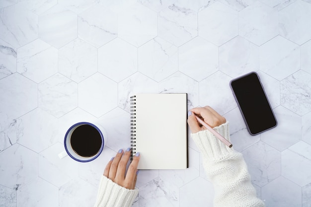 Flat lay of woman writing on blank notebook and drinking hot cup of coffee and using smartphone on white marble
