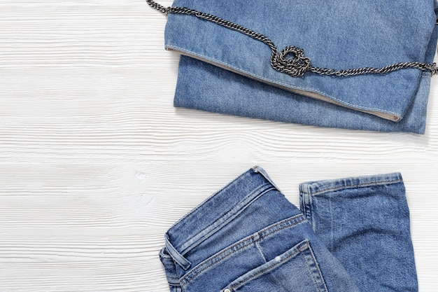 Flat lay of women casual fashion outfits on white wooden background, blue jeans and denim small bag. female clothing with copy space.