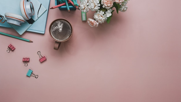 Flat lay women office desk with notebook coffee cup, pink bouquet and stationery