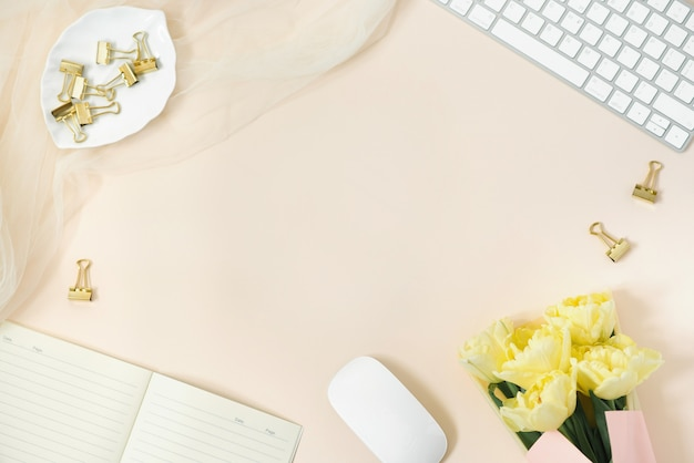 フラット横たわっていた女性のオフィスデスク。キーボード、チューリップの花束、アクセサリー、日記、コピースペースとベージュの用紙の背景にメガネの女性のワークスペース。トップビューの女性的な背景。