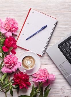 평평한 여자 사무실 책상. 흰색 바탕에 노트북, 분홍색 모란 꽃다발, 커피가 있는 여성 작업 공간. 상위 뷰 여성 배경입니다.