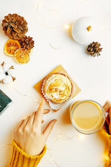 Flat lay of womens hands touching coffee mug and tartlet girl in sweater is having breakfast sweet d...