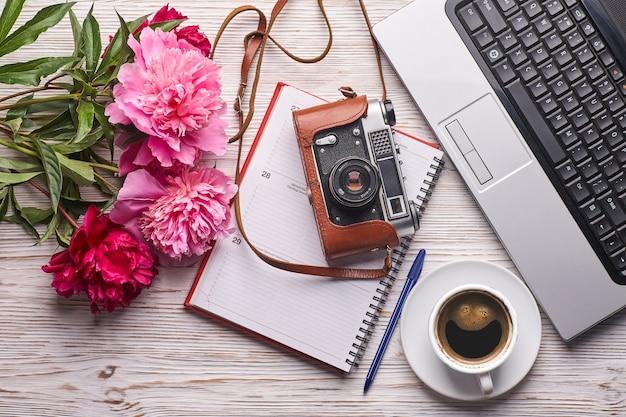 노트북 분홍색 모란 꽃다발 카메라와 커피가 있는 평평한 여성 사무실 책상 여성 작업 공간