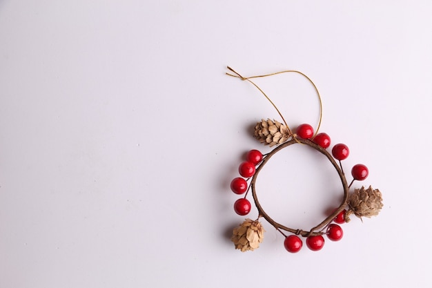 Flat lay of wooden christmas ornament with small pine cones isolated on white