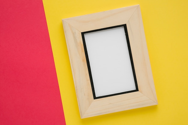 Flat lay wooden frame with bicolor background