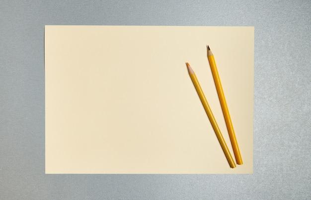 Плоская планировка. деревянные карандаши на листе желтой бумаги. вид сверху желтых инструментов на сером фоне