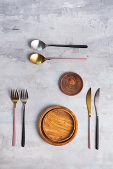 Flat lay of wooden plate and cutlery utensils on grey . empty plate. ,food, zero waste .
