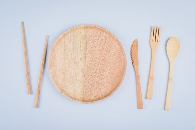 Flat lay of wooden plate and cutlery utensils