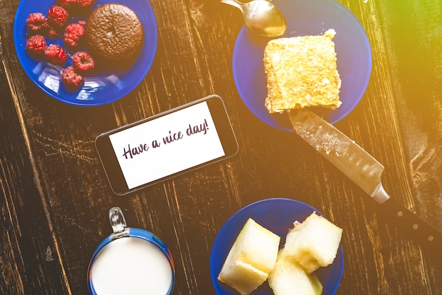 Flat lay on wooden table with food for breakfast with text on the phone have a nice day. milk, pankakes and fruits a