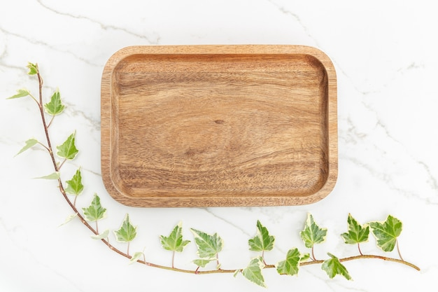 Flat lay of wooden tray and green ivy leaves on white marble background. mock up