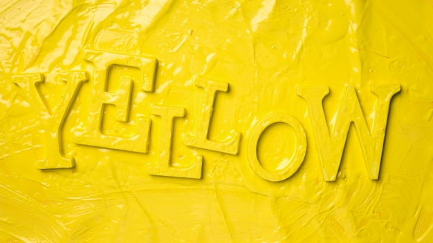 Flat lay of word yellow with paint