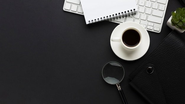 Flat lay of work desk with coffee cup and magnifying glass