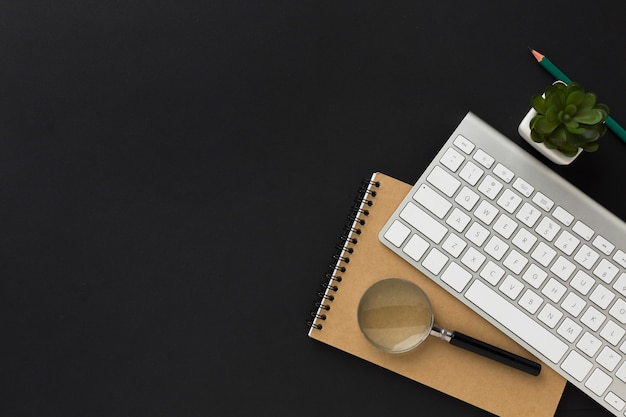Flat lay of work desktop with notebook and keyboard
