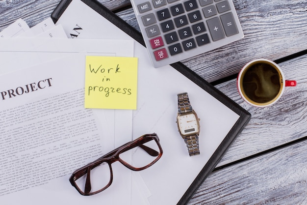 평면 누워 작업 진행 중인 개념입니다. 흰색 나무 테이블에 계산기와 커피 컵이 있는 비즈니스 프로젝트 서류.