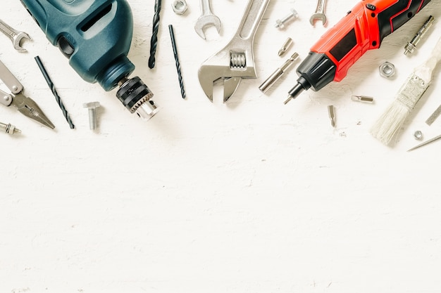 Flat lay of working construction tools on grunge white wood.