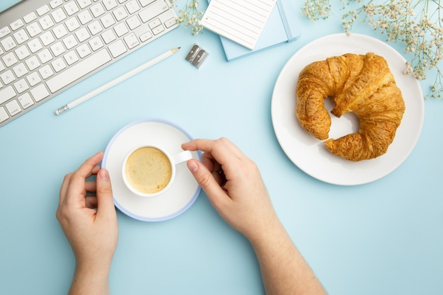 Flat lay workplace arrangement on blue background with breakfast meal
