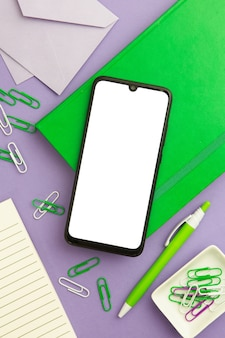 Flat lay workplace arrangement on purple background with empty phone
