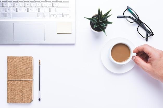 Плоская планировка, рабочее место с ноутбуком, рука с кофе и блокнотом и ручкой на столе.