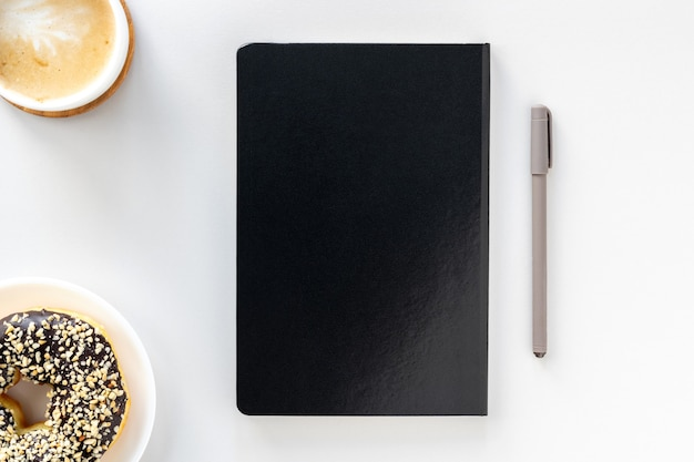 Flat lay of workspace desk, black notepad, pen, coffee and chocolate donut
