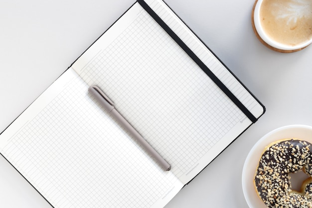 Flat lay of workspace desk, open notebook, pen, coffee and chocolate donut