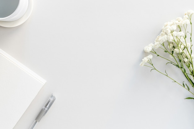 Flat lay of workspace desk with paper notepad, pen, pure water and gypsophila flowers