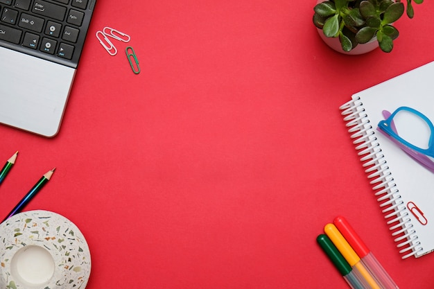 Flat lay workspace red desk with laptop and office stationery. business lady blog hero concept.