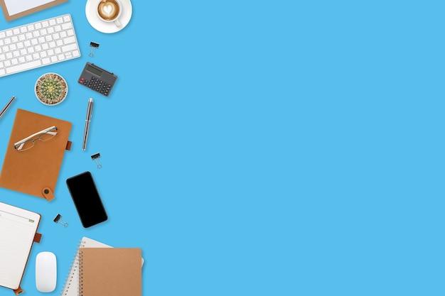 Плоский рабочий стол с портативным компьютером, канцелярскими принадлежностями, чашкой кофе, планшетом и мобильным телефоном на синем пастельном фоне