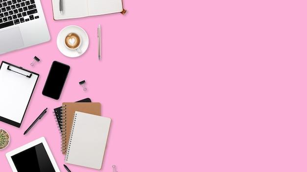 Плоский рабочий стол с портативным компьютером, канцелярскими принадлежностями, чашкой кофе, планшетом и мобильным телефоном на розовом пастельном фоне