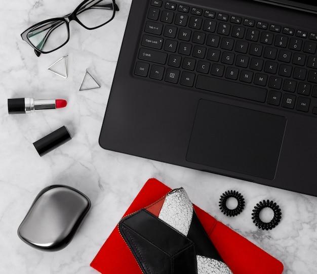 노트북, 플래너, 안경, 휴대 전화, 귀고리, 머리 넥타이, 빗 및 립스틱이있는 평평한 작업 공간. 세련된 사무실 대리석 책상.
