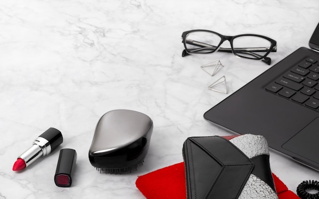Flat lay workspace with laptop, planner, glasses, mobile phone, ear rings, hair tie, comb and lipstick. stylish office marble desk.