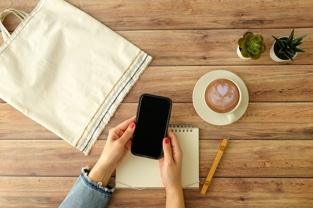 Flat lay workspace. woman hand with coffee cup, smartphone, computer, notebook, planner and stationary with copy space. top view.