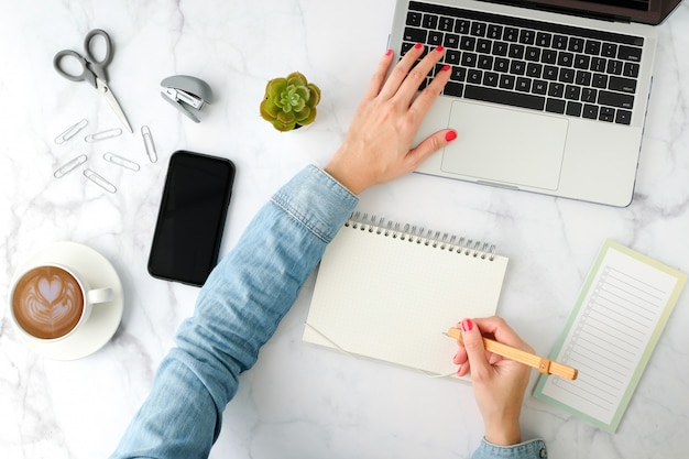 Flat lay workspace. woman hand with coffee cup, smartphone, computer, notebook, planner and stationary with copy spacetop view.