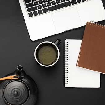 Flat lay of workstation with cup of tea and notebooks